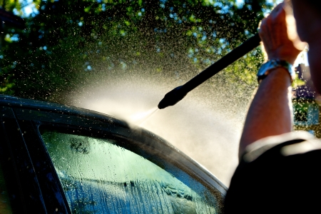 man washing car in sunshine with high pressure washer photo