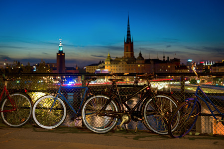 parked bicycles: Bicycles parked at Slussen at night in Stockholm, with the city hall in background