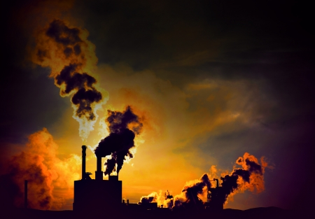 Silhouette of factory with chimneys and heavy orange smoke at night Standard-Bild