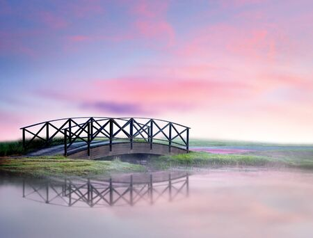 small wooden foot bridge reflected in water in foggy morning photo