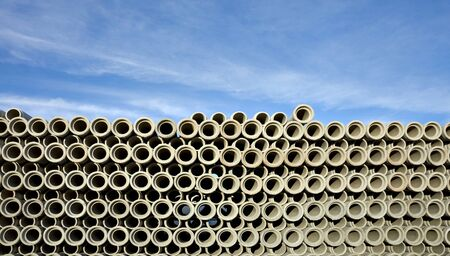 drainage: Huge stack of concrete drainage pipes on blue sky