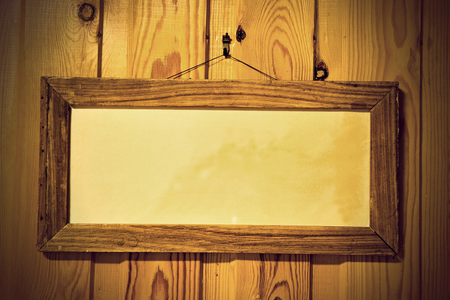 framed picture: Simple wooden picture frame with aged yellow paper on wooden knotted wall