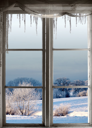 winter window: Beautiful winter landscape with rime frost in bushes and trees, seen through an old window with icicles