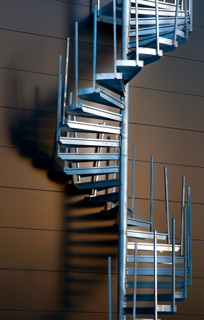 Metal spiral staircase casting shadow on wall in evening light photo