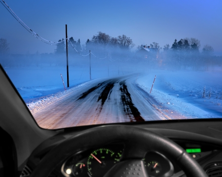 windscreen: Rural road in cold foggy winter evening seen through windscreen of car Stock Photo