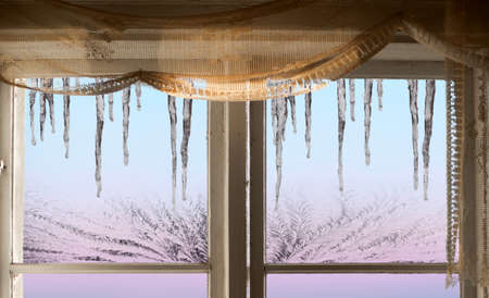winter window: Icicles on blue, pink and and purple sky viewed through old window with ice crystals Stock Photo