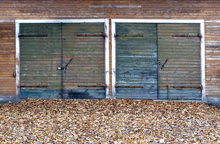 door leaf: Garage doors made of knotted wood in autumn Stock Photo