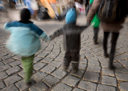 Legs of kids in blurred motion walking on street with cobble stones
