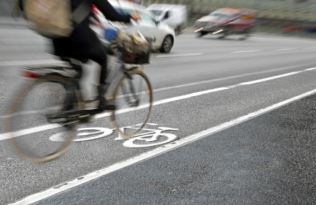 Female cyclist in bicycle lane on busy street photo