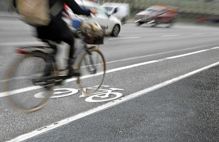 Kobieta rowerzysta na ścieżce rowerowej na ruchliwej ulicy Zdjęcie Seryjne