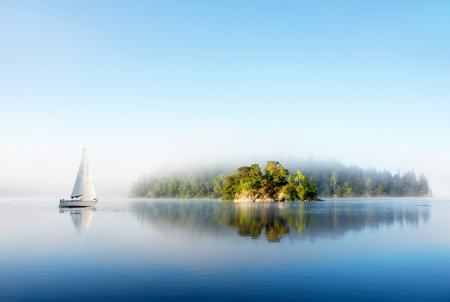 Island and yacht reflected in clear blue Scandinavian lake on foggy sunny morning