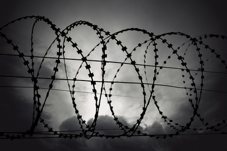 Barbed wire on moody gloomy gray sky Stock Photo - 23800652