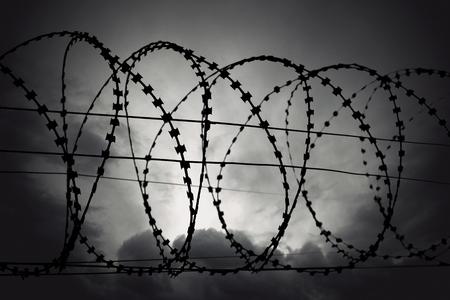 gloomy: Barbed wire on moody gloomy gray sky