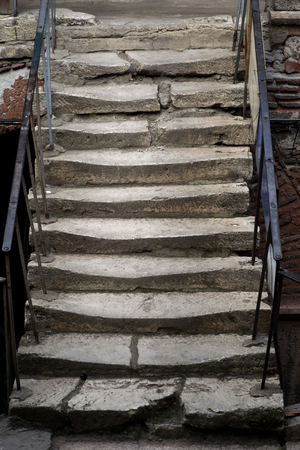 broken up: Ancient stone staircase with metal handrail