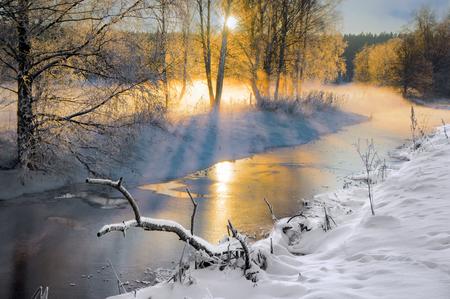 Scandinavian small river in winter, with sunbeams filtering through bare birch trees Standard-Bild