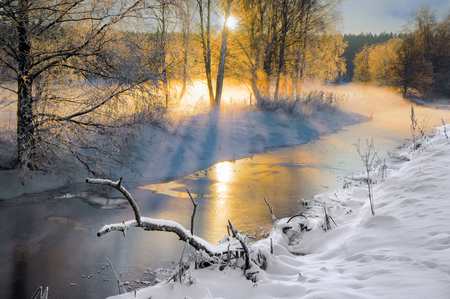 Scandinavian small river in winter, with sunbeams filtering through birch trees