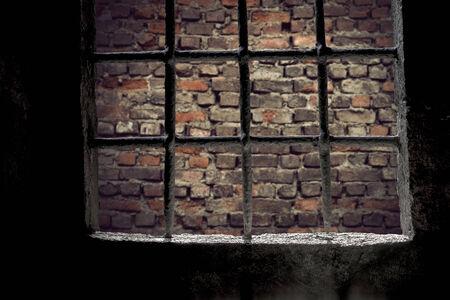 jailhouse: Brick wall viewed through prison window with metal bars