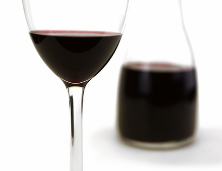 carafe: Glass of red wine isolated on white with carafe in background