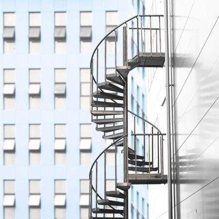 Spiral staircase with bright blue wall of office building in background photo