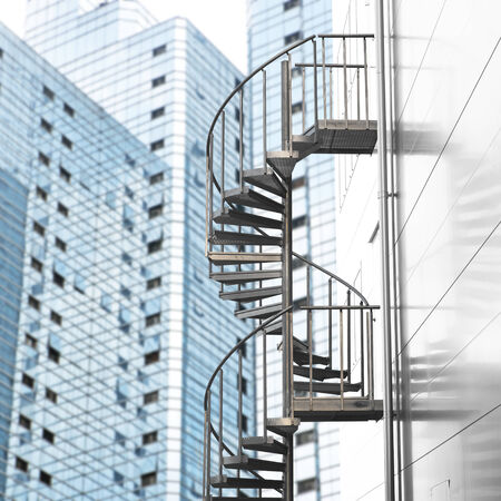 Spiral staircase with modern buildings in background photo