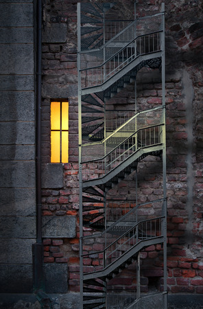 dark alley: Spooky old building in dark alley with small lit window and metal fire escape
