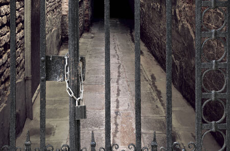 dungeons: Door with metal bars locked with chain and padlock in front of dark cellar passage