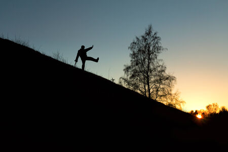 Happy photographer on small hill at sunset photo