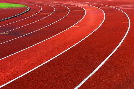 Curve of running tracks in athletics stadium, one lane highlighted photo