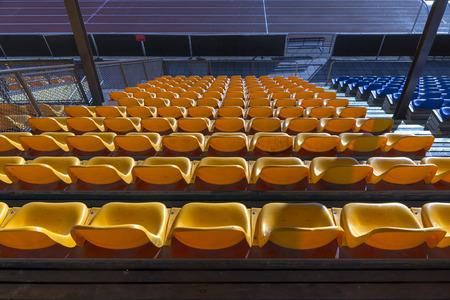 Rows of empty yellow plastic seats at sports stadium photo