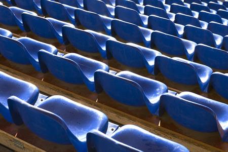 Rows of empty blue plastic seats at sports stadium photo