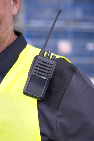 walkie-talkie on shoulder of man i yellow vest Stock Photo