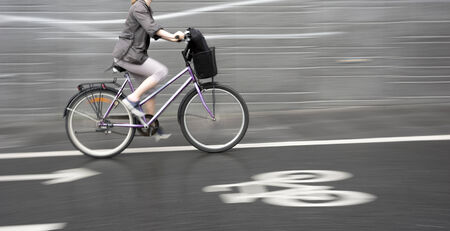 haste: Young woman on purple bike with smooth gray blurred background