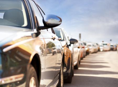Wiersz zaparkowanych samochodów z odbiciem ruchu i budynków