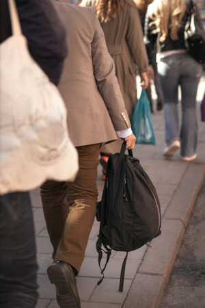 packer: back of man in beige clothes with back packer on sidewalk