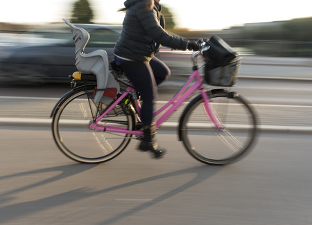 child seat: woman in blurred motion on pink bicycle with child seat