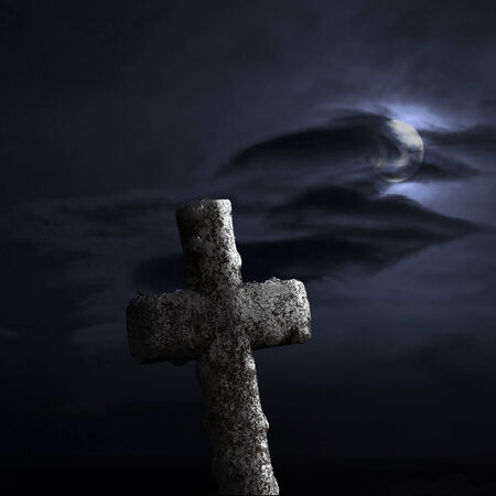 christian halloween: Stone cross on dramatic sky with moonshine