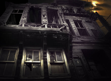 broken house: Spooky wooden building on moody night sky with full moon