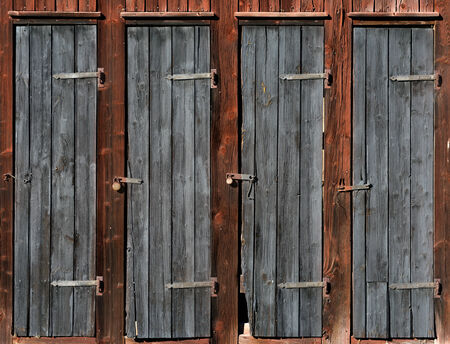 bad condition: Row of doors on wooden shed in bad condition