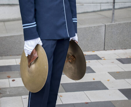 cymbals: Young man with two cymbals in marching band