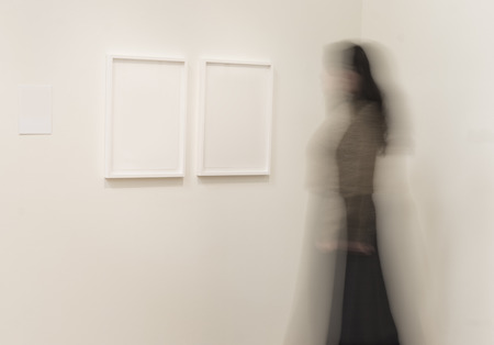 exhibition: Blurred woman looking at pictures in a musesum