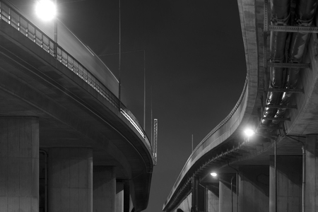 Low angle view of elevated road in black and white at night photo