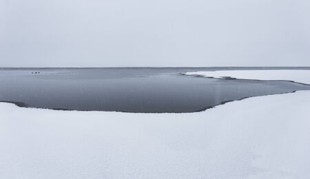 sparse: Sparse winter landscape with snow and ice on lake as well as open water
