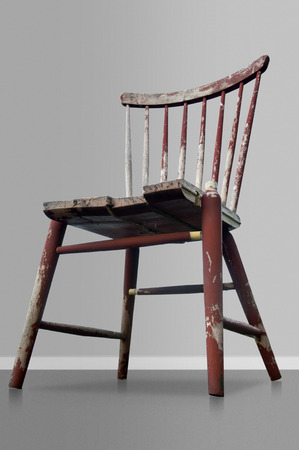 tatty: Old worn red wooden chair on gray background