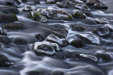 streaming: Rocks in streaming water with caps of ice, long exposure Stock Photo
