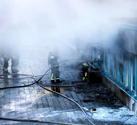 building on fire: Firemen working to extinguish fire in building Stock Photo