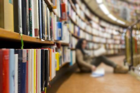 Kobieta z książki siedzi na podłodze w bibliotece