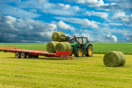 Tractor and trailer with hay bales in rural landscape
