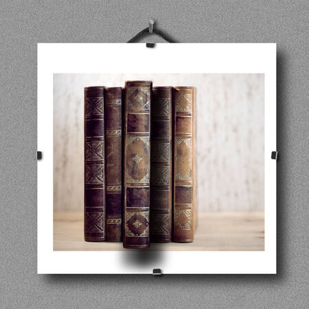 pulled: Picture of vintage books hanging on wall, with  3d illusion that one book is pulled out of the picture