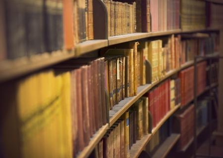 Bibliotheek of boekhandel met rijen van oude antieke boeken Stockfoto