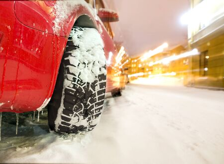 Studded tyre of red car on street in winter evening photo
